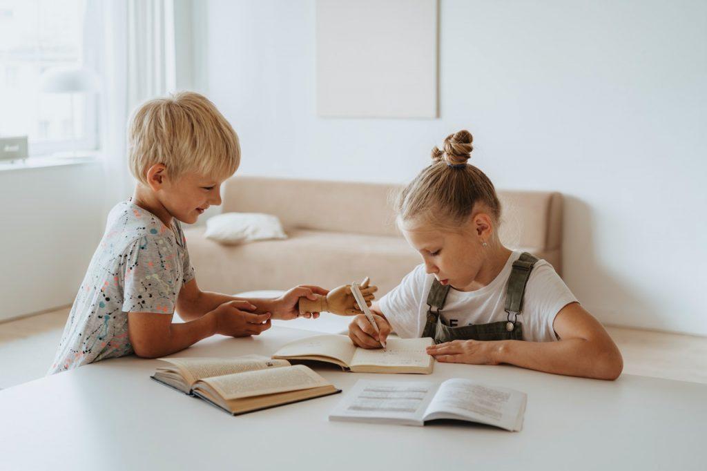 fille et garçon qui font leurs devoirs